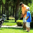 Father teaching son playing golf — Stock Video #49378879