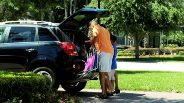 Boy helping parents pack car — Stock Video