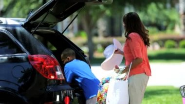 Boy helping parents pack car — Vídeo de stock
