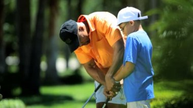 Boy learning to play golf — Vídeo de stock