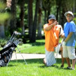 Father teaching son playing golf — Stock Video #49380385