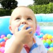 Smiling Little Boy Playing at Plastic Ball Pool Outdoors — Stock Video #49572059