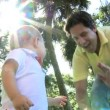 Loving young Caucasian father enjoying visit outdoors park playing big blue ball with smiling toddler son — Stock Video #49573401
