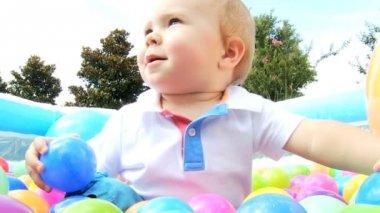 Caucasian boy having fun at  playing plastic ball pool — Stock Video