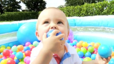 Smiling Little Boy Playing at  Plastic Ball Pool Outdoors — Stock Video