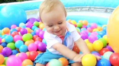 Caucasian boy toddler sitting in multi coloured plastic balls — Stock Video