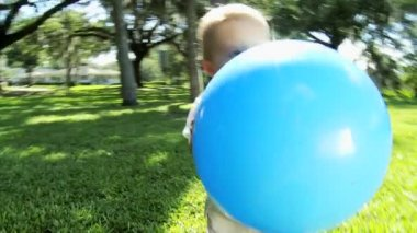 Happy Little Boy Walking on  Park Grass with Giant Ball — Stock Video