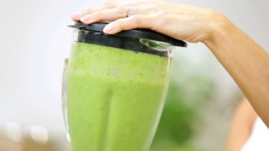 Female preparing for workout session by  making fresh organic vegetable juice — Stock Video