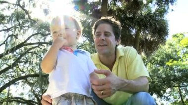 Cute Caucasian boy toddler having fun outing at park with laughing young father — Vídeo Stock