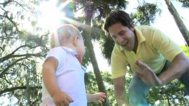 Loving young Caucasian father enjoying visit outdoors park playing big blue ball with smiling toddler son — Stock Video