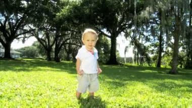 Healthy happy young male Caucasian child practicing walking grass outdoors park — Stock Video