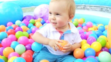 Laughing Caucasian baby boy having fun with parents playing in multi coloured ball pool — Stock Video