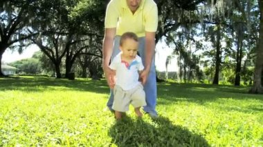Boy enjoying walking barefoot over grass with his  loving young father — Stock Video