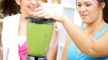 Girls came home from gym and making nutritious fresh homemade vegetable juice drink — Stock Video