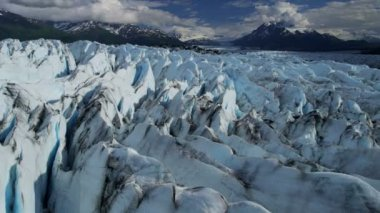 Aerial view of moraine covered Knik Glacier and crevasses feeding the Knik River which empties Cook Inlet east of Anchorage Alaska, USA shot on RED EPIC — Stock Video