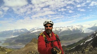 Male mountain Peak climber filming glacier melt waters — Wideo stockowe