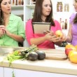 Smiling young Caucasian girl at home kitchen with sister and mom holding wireless tablet — Stock Video #49654697