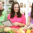 Young Caucasian girl at home kitchen with mother and sister using wireless tablet — Stock Video #49654729