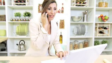 Caucasian businesswoman hearing news and working at  home kitchen using laptop — Stock Video