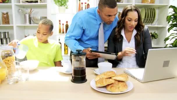 Familia en la cocina preparando con tablet y laptop — Vídeo de stock