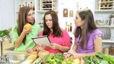 Teenage Caucasian girl with  mom and sister at home kitchen using wireless tablet — Stockvideo