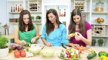 Mom at home kitchen watching as teenage daughters slicing fresh organic vegetables — Stock Video
