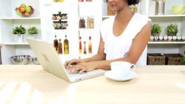 Girl at kitchen using laptop — Stock Video