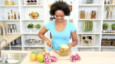 Female at kitchen cutting pineapple — Stockvideo