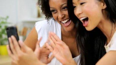 Girlfriends using smartphone in kitchen — Stock Video
