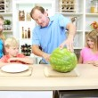 Father slicing watermelon for family — Stock Video #50340345