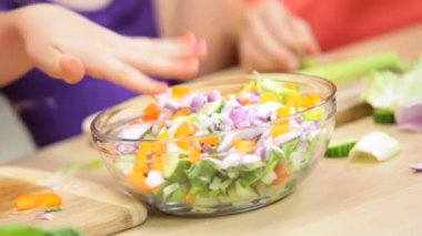 Girl mixing chopped salad vegetables — Stock Video
