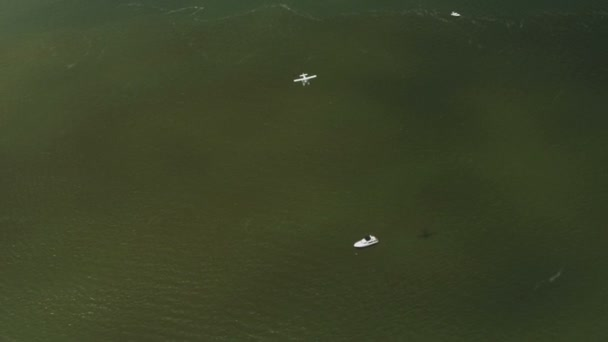 Aerial view of flying seaplane passing above cruiser, — Vidéo