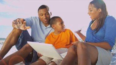 Family on beach using laptop — Stock Video