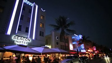 Night driving across illuminated restaurants — Vidéo