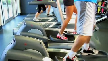 Gym members on exercise equipment — Stock Video