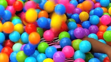 Girl covered colored plastic balls — Stock Video