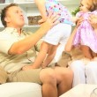 Parents playing with daughters on sofa — Stock Video #51651575