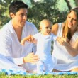 Young couple playing with baby in the park — Stock Video #51658717