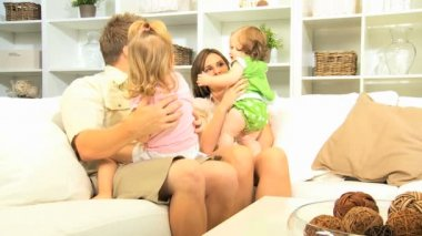 Girls playing with parents on couch — Stock Video