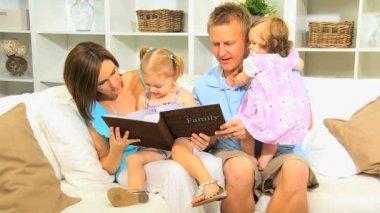 Young Family Enjoying Photograph Album Close Up — Stock Video