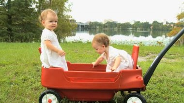 Twin girls standing in plastic cart — Stock Video