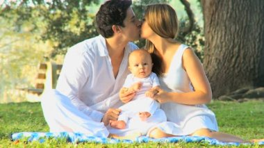 Young couple kissing with baby in her arms — Stock Video