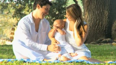 Young couple playing with baby in the park — Stock Video