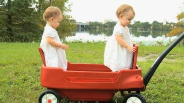 Twin girls standing in plastic cart — Stock Video