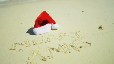Santa Hat Beside Christmas Greeting  in Sand — Stock Video