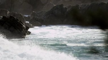 Waves swirling around jagged rocks — Stock Video