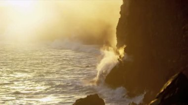 Steam from boiling lava flows beside jagged coastal rocks — Stock Video