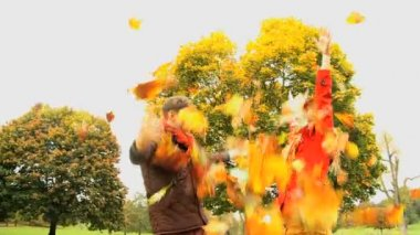 Happiness of young Caucasian couple playing with autumn leaves — Stock Video