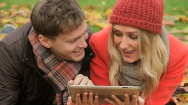 Couple surfing wireless tablet in park — 图库视频影像