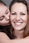 Playful Daughter is kissing her mother on the cheek — Stock Photo